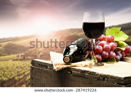 sunset with landscape of tuscany and bottle wine leaves and fruits  - stock photo