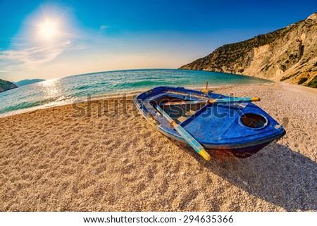 Sunset with Old Blue Boat on Empty Myrtos Beach on Kefalonia Island of Greece - stock photo