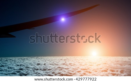 sunset with plane wing in the air - stock photo
