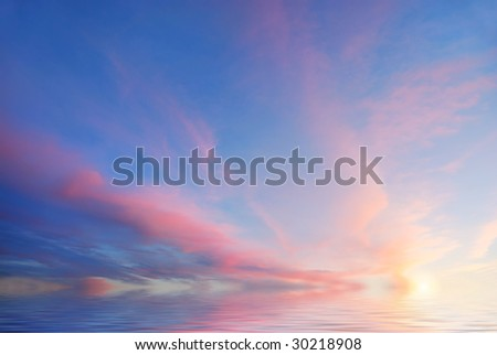 Sunset with purple clouds and blue sky reflecting in water.