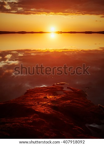 Sunset with red color in the clouds and the rocks on the shore. Dramatic reflection of the Sun in the still water of a lake in Finland. - stock photo