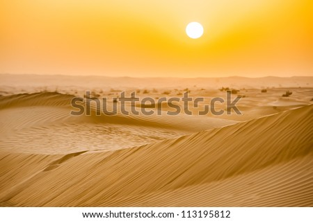 Sunset with sand dunes in desert - stock photo