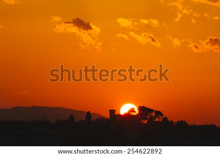 Sunset with silhouette of a castle - stock photo
