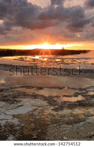 Sunset with sun beams above a hot spring, Yellowstone National Park, Wyoming, USA. - stock photo