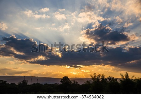 Sunset with sun rays shining through the clouds. - stock photo