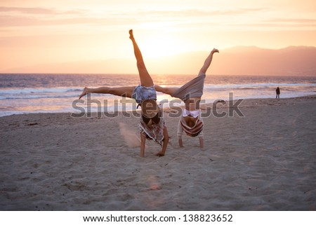 Sunset with Two Beautiful Woman doing cartwheels on the Beach in Santa Monica California - stock photo