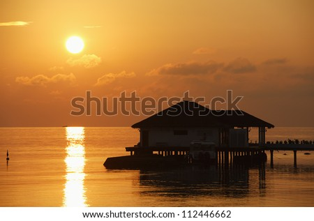 Sunset with water bungalow in the Indian Ocean, Maldives - stock photo