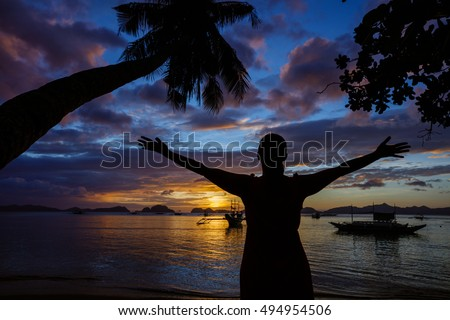 Sunset with woman, palm and boat in the Palawan Island in the Philippines.