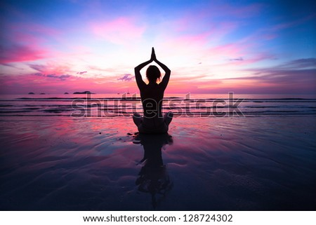 Sunset yoga woman on sea coast. - stock photo