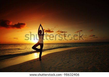 sunset yoga woman on sea coast - stock photo