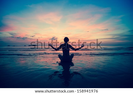 Sunset yoga woman on sea coast (in cold colors) - stock photo