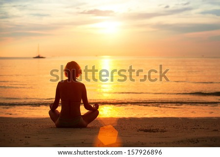 Sunset yoga woman practicing on the sea beach.