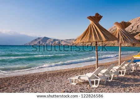 Sunshade and deck chair on beach at Baska in Krk - Croatia - stock photo