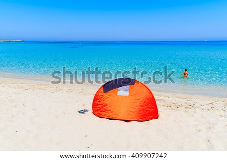 Sunshade tent on sandy Bodri beach and young boy relaxing in water, Corsica island, France