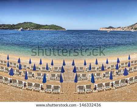 Sunshades and blue deck chairs on beach at Dubrovnik - Croatia - stock photo