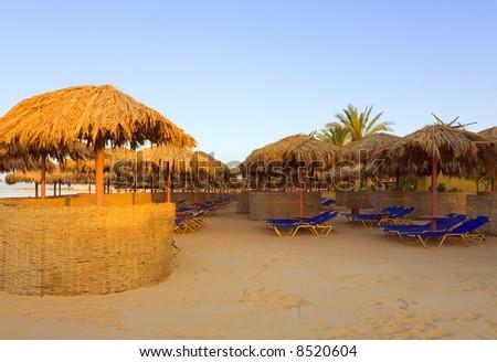 Sunshades on a tropic beach at sunset. - stock photo