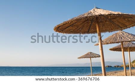 Sunshades on the sandy tropical beach summer travel destination  - stock photo