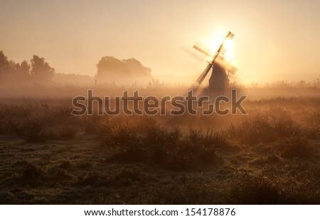 sunshine behind windmill in morning fog, Holland - stock photo