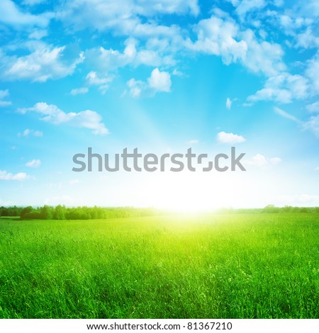 Sunshine in blue sky and green field. - stock photo