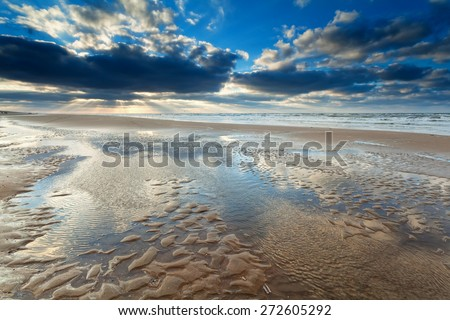 sunshine over North sea beach at low tide, Netherlands - stock photo
