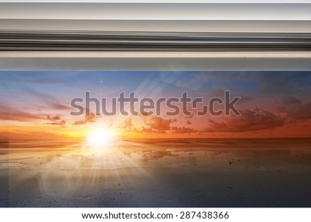 Sunshine over seascape through window with rolled up curtain