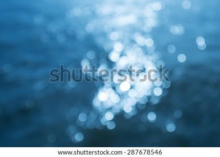 Sunshine reflections on blue water - stock photo