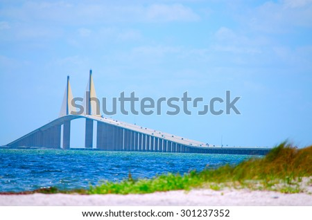 Sunshine Skyway Bridge crossing Tampa Bay in Florida with a beach in the foreground - stock photo