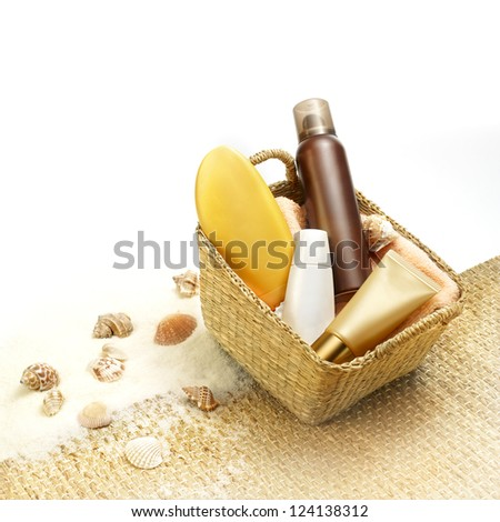 Suntan creams in a beach basket - stock photo