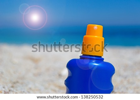 suntan lotion bottle in the sand - stock photo