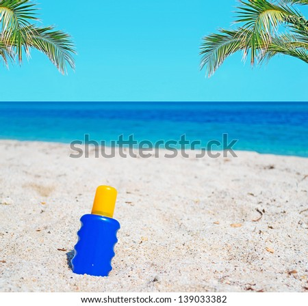 suntan lotion bottle in the sand with palms - stock photo