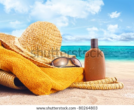 Suntan lotion, straw hat with towel at the beach - stock photo