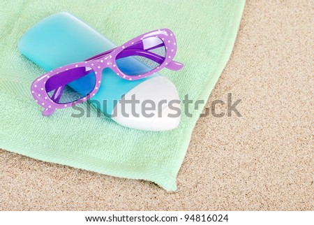 Suntan lotion sun glasses and beach towel