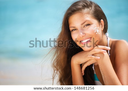 Suntan Lotion Woman Applying Sunscreen Solar Cream. Beautiful happy cute Girl applying Sun Tan Cream on her Face with ocean in background. Sun Tanning. Skin Protection - stock photo