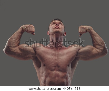 Suntanned shirtless fitness male model isolated on a grey background.