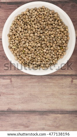 Super food hemp seed in white bowl over wooden background