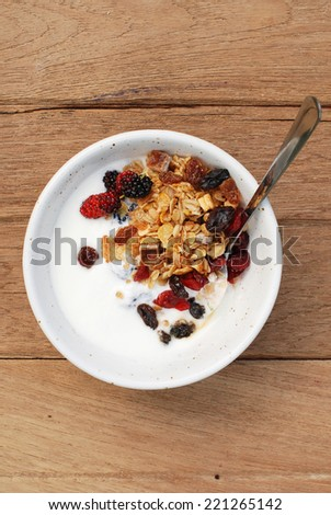 super food , homemade yogurt with muesli, dried raspberry, raisin, fresh organic mulberry, in a bow on wooden table. brunch - stock photo