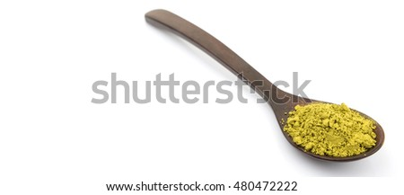Super food moringa powder in wooden spoon over white background