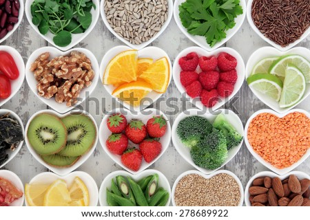 Super food selection for health diet in porcelain bowls over distressed wooden background.  - stock photo