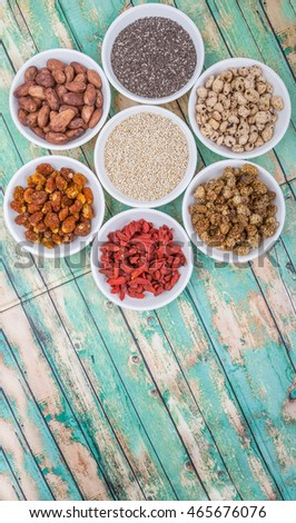 Super food tiger nuts, mulberry berries, cacao beans, goji berries, quinoa seeds, golden berry, chia seed in white bowls over wooden background