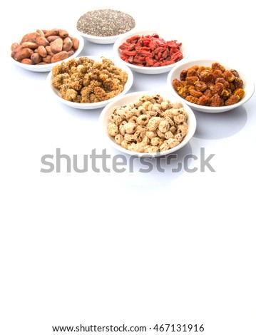 Super food tiger nuts, mulberry berries, cacao beans, goji berries, quinoa seeds, golden berry in white bowls over white  background