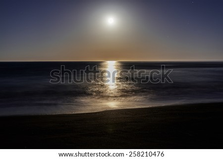Super / Full Moon setting / rising on Moonstone Beach, along the Big Sur Highway, on the California Central Coast, near Cambria CA. - stock photo