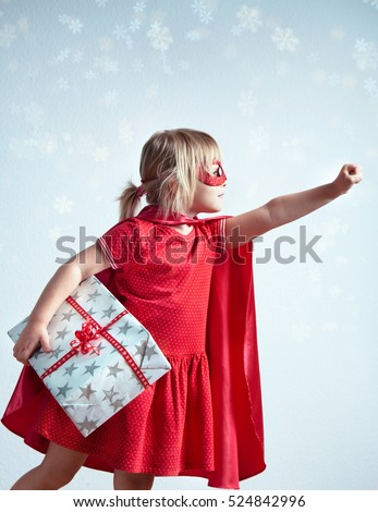 Super gifts for super kids or Special delivery for Christmas. Little girl wearing a superhero costume and a mask posing as a superhero and holding a big gift box. Toned photo with digital snow effect.