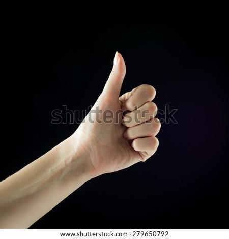 Super good. Thumb up. Female hand. Finger. Isolated on black background. - stock photo