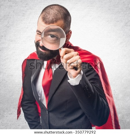 Super hero businessman with magnifying glass - stock photo