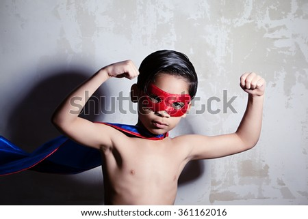 Super Strength.  Young, mixed race boy dressed in a cape and mask and flexing his muscles.  Dramatic lighting with dark shadow cast in the background.