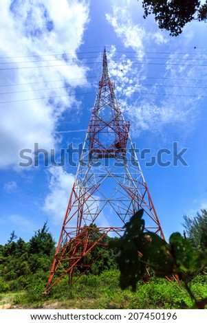 Super wide angle photograph of Electricity pylon with blue sky and white clouds - stock photo