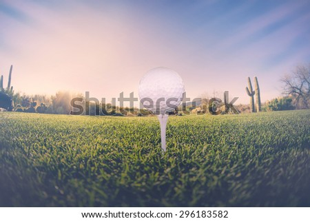 Super wide angle view of golf ball on tee with desert fairway and stunning Arizona sunset in background - stock photo