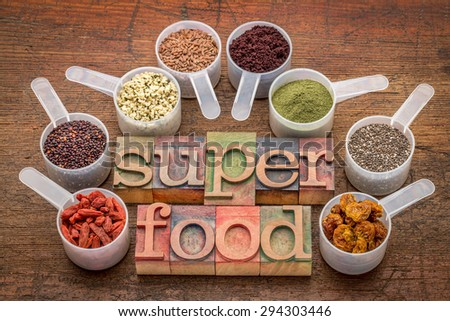superfood abstract (wheatgrass, acai berry, goji berry, falx seed,chia seed,goldenberry,hemp seed, quinoa grain) - a set of measuring scoops with la letterpress text against rustic wood - stock photo
