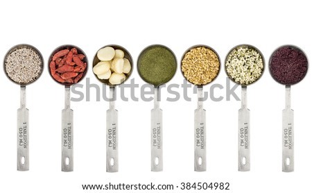 superfood abstract - white chia seeds, goji berry,macadamia nuts, barley grass powder, golden flax seeds, hemp seeds and acai berry powder - top view of  metal measuring tablespoons isolated on white - stock photo