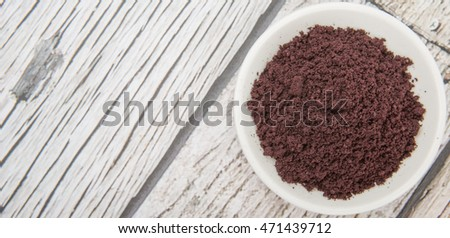 Superfood dried acai berry powder in white bowl over wooden background